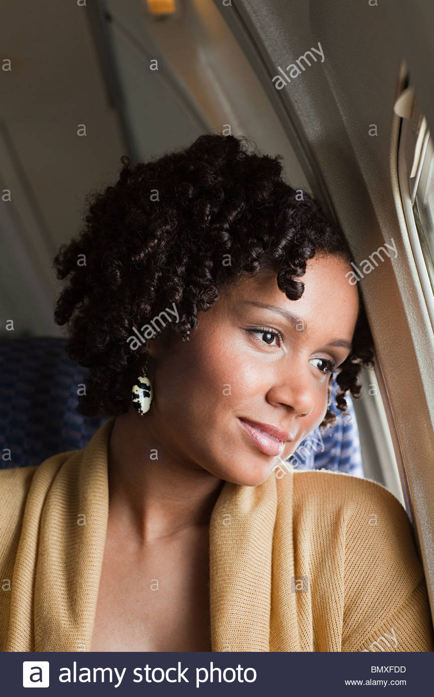 Female airplane passenger looking out of window - Stock Image
