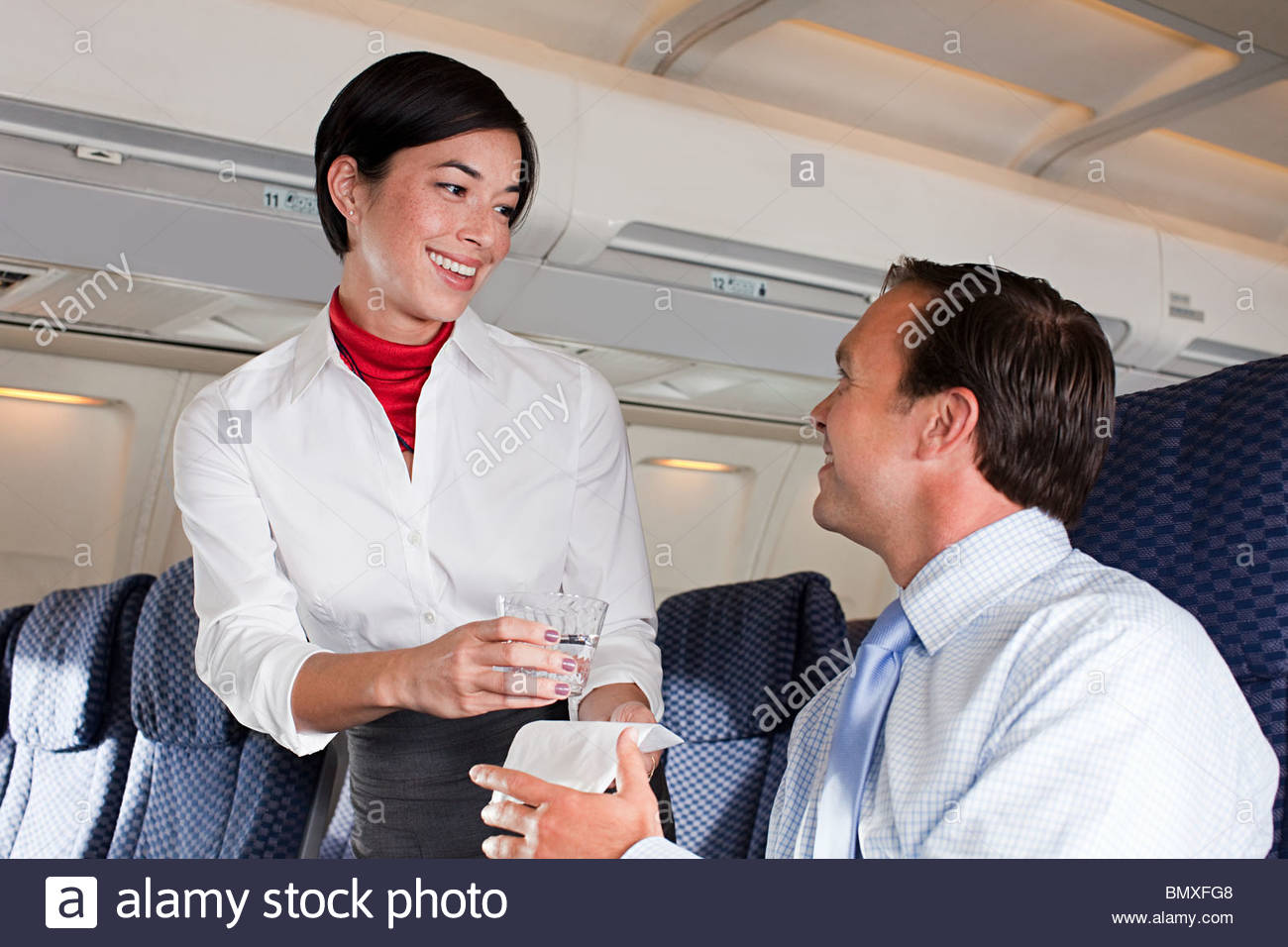 Air stewardess giving drink to passenger - Stock Image