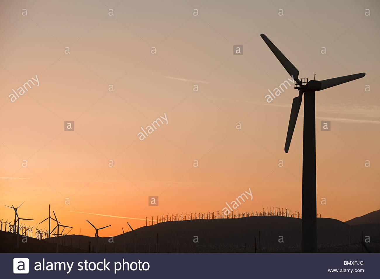 Silhouettes of wind turbines at sunset - Stock Image