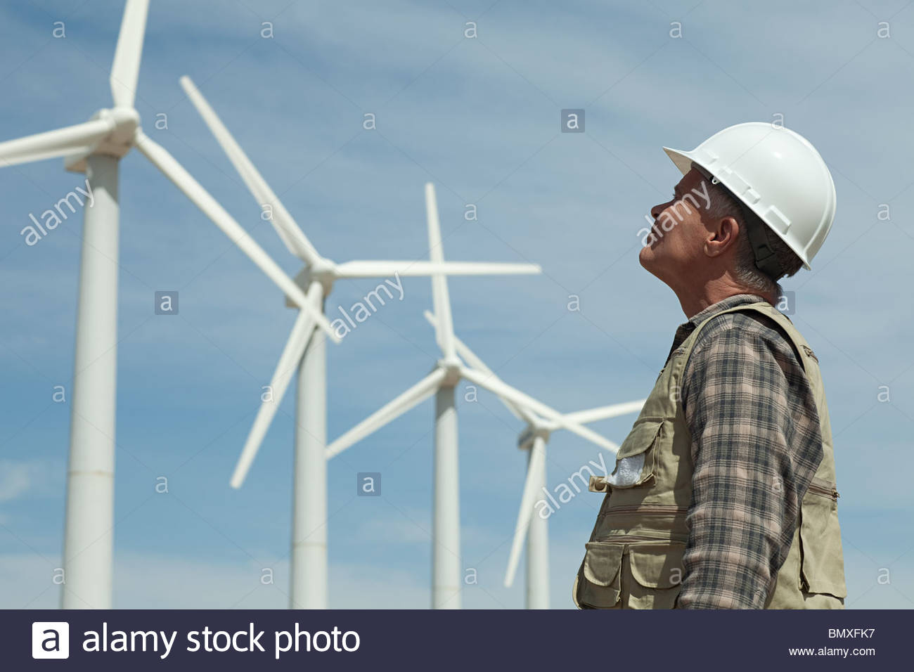 Man in hard hat looking at wind turbines - Stock Image