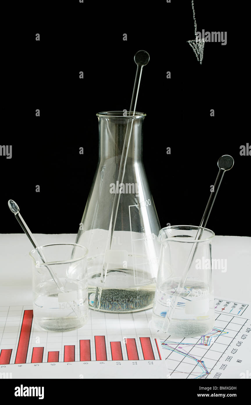 Flask and beakers on graphs Stock Photo