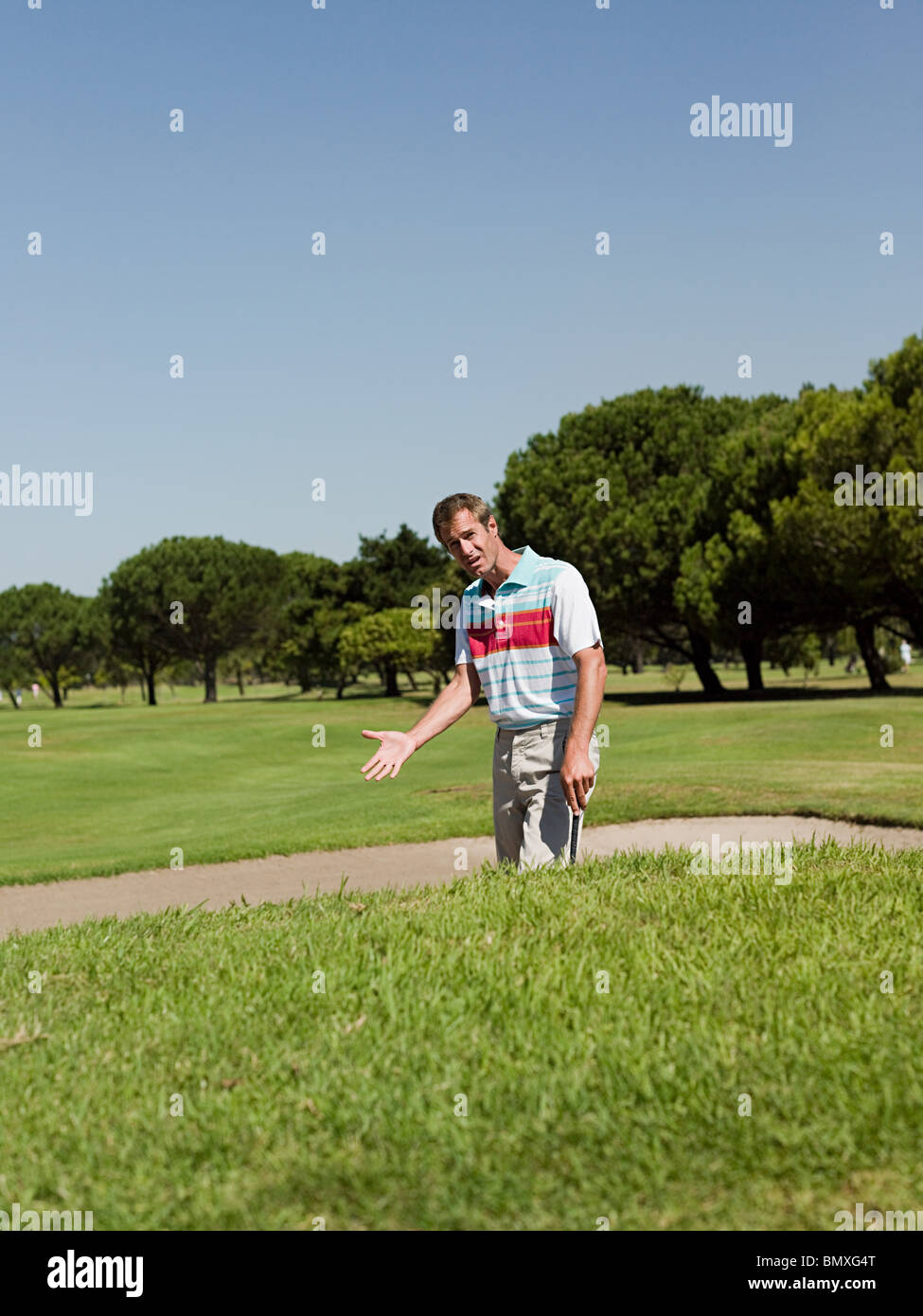 Man playing golf, stuck in bunker - Stock Image