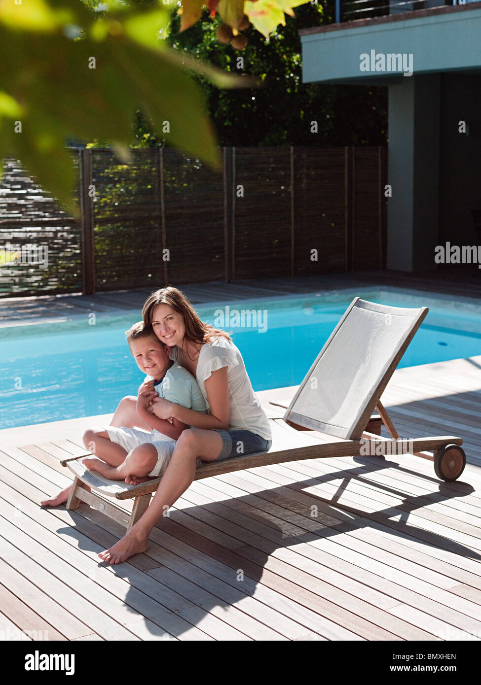 Boy and mother on chair by pool - Stock Image