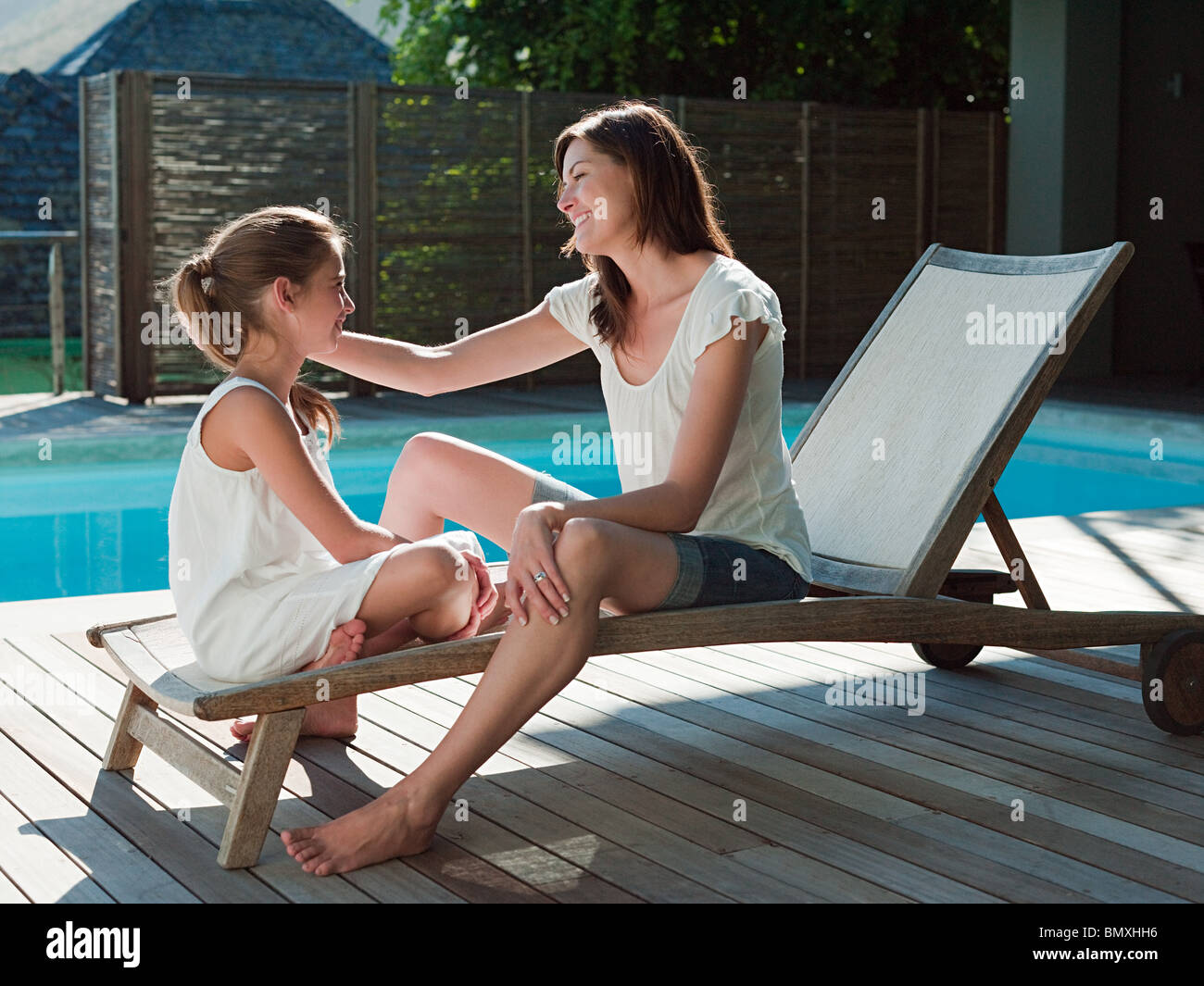 Girl and mother on lounge chair by swimming pool Stock Photo