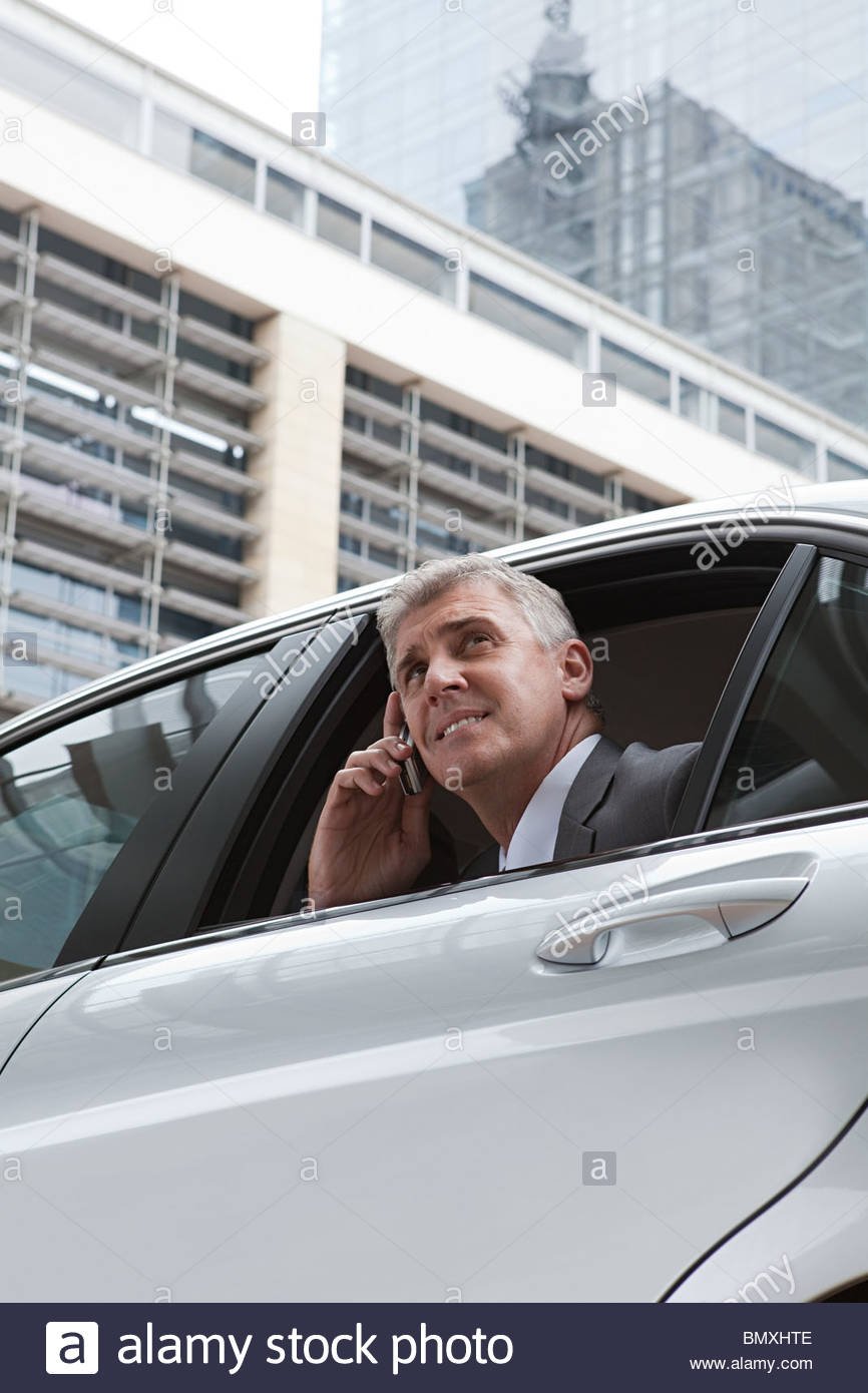 Businessman on cellphone in car - Stock Image