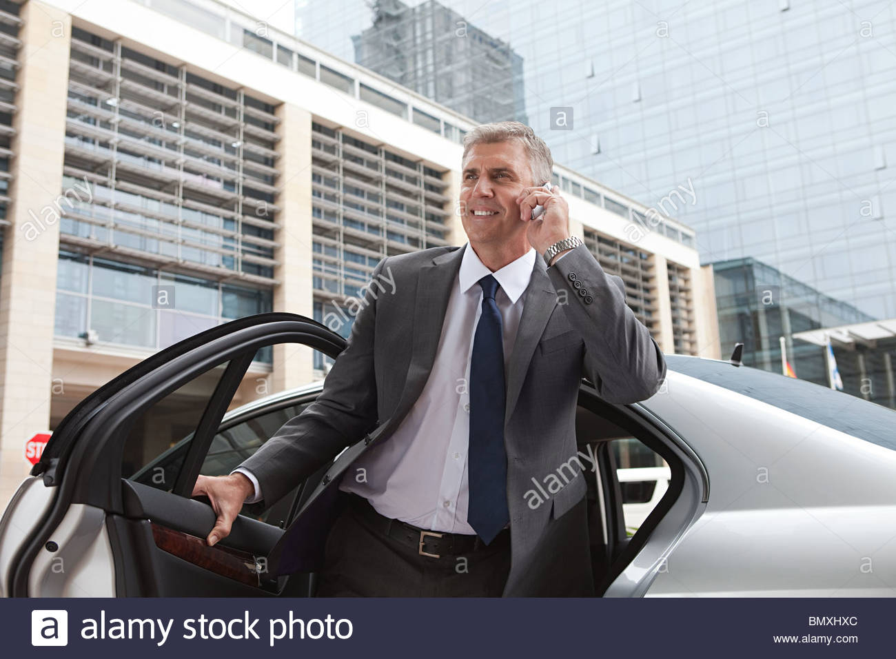 Businessman on cellphone getting out of car - Stock Image
