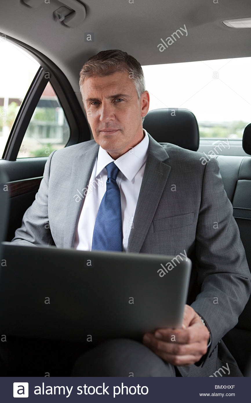 Businessman in car with laptop - Stock Image