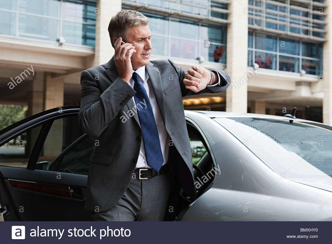 Businessman on cellphone looking at watch - Stock Image