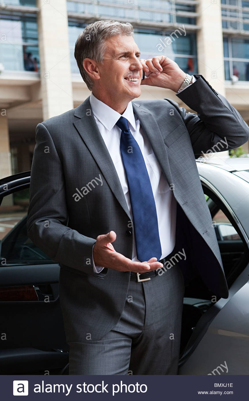 Businessman on cellphone by car Stock Photo