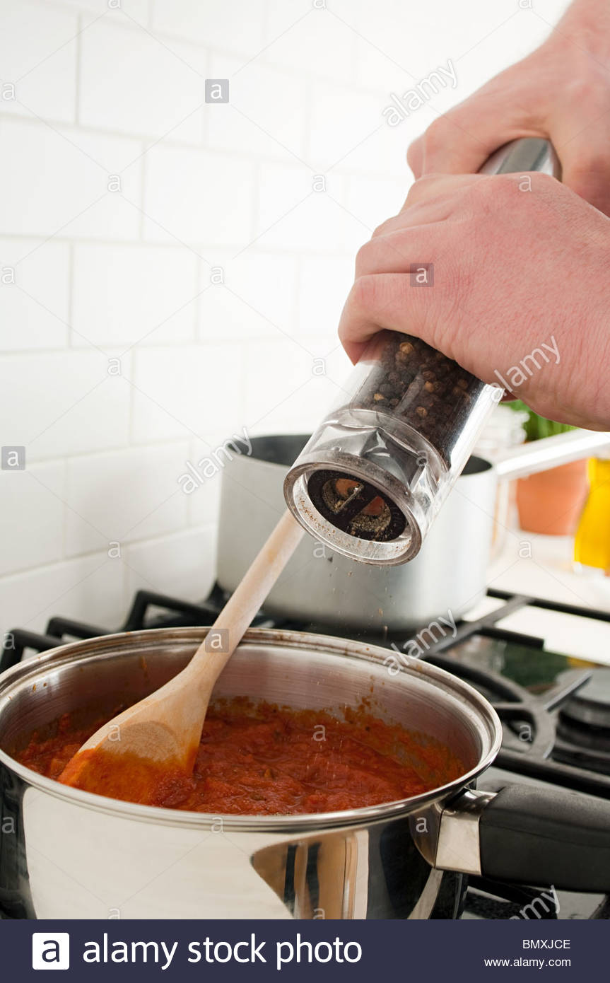 Man grinding pepper into saucepan - Stock Image