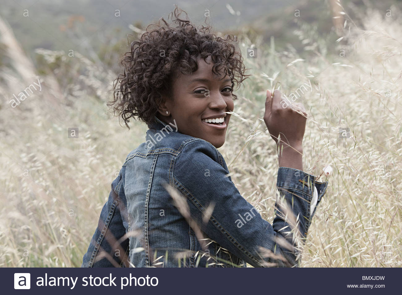 Young woman looking over shoulder - Stock Image