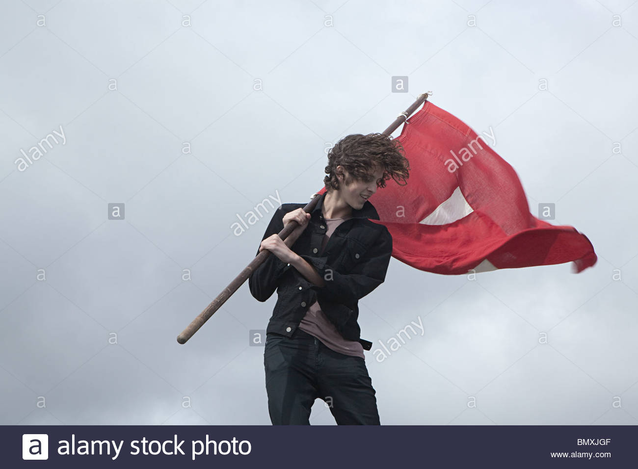 Teenage boy with red flag - Stock Image