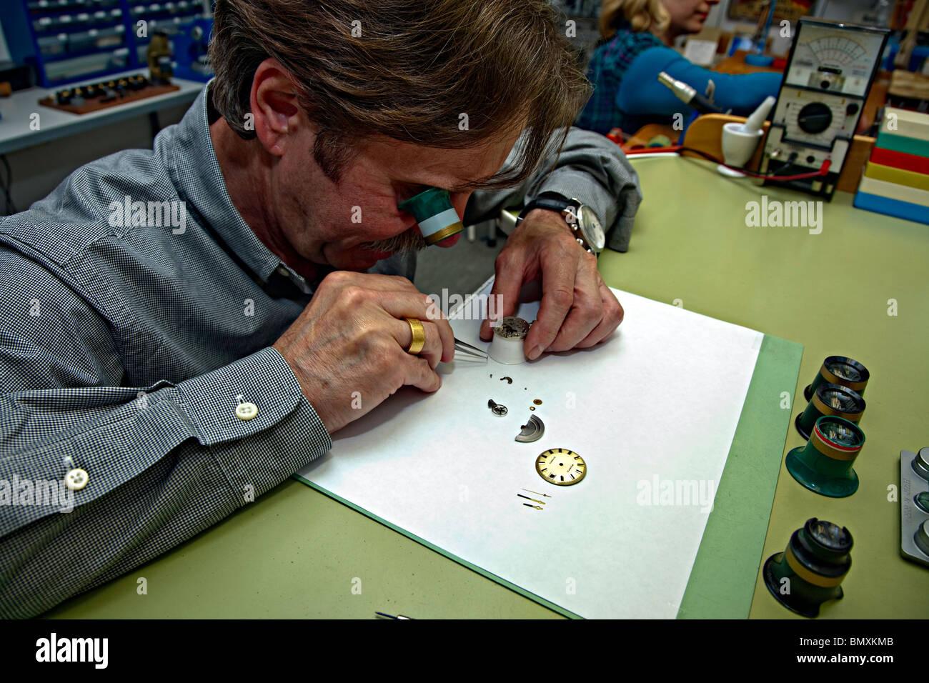 watchmaker Uhrmachermeister juwelier Goldschmiede clock mechanism technician repair replacement cleaning Lope clockmaker - Stock Image