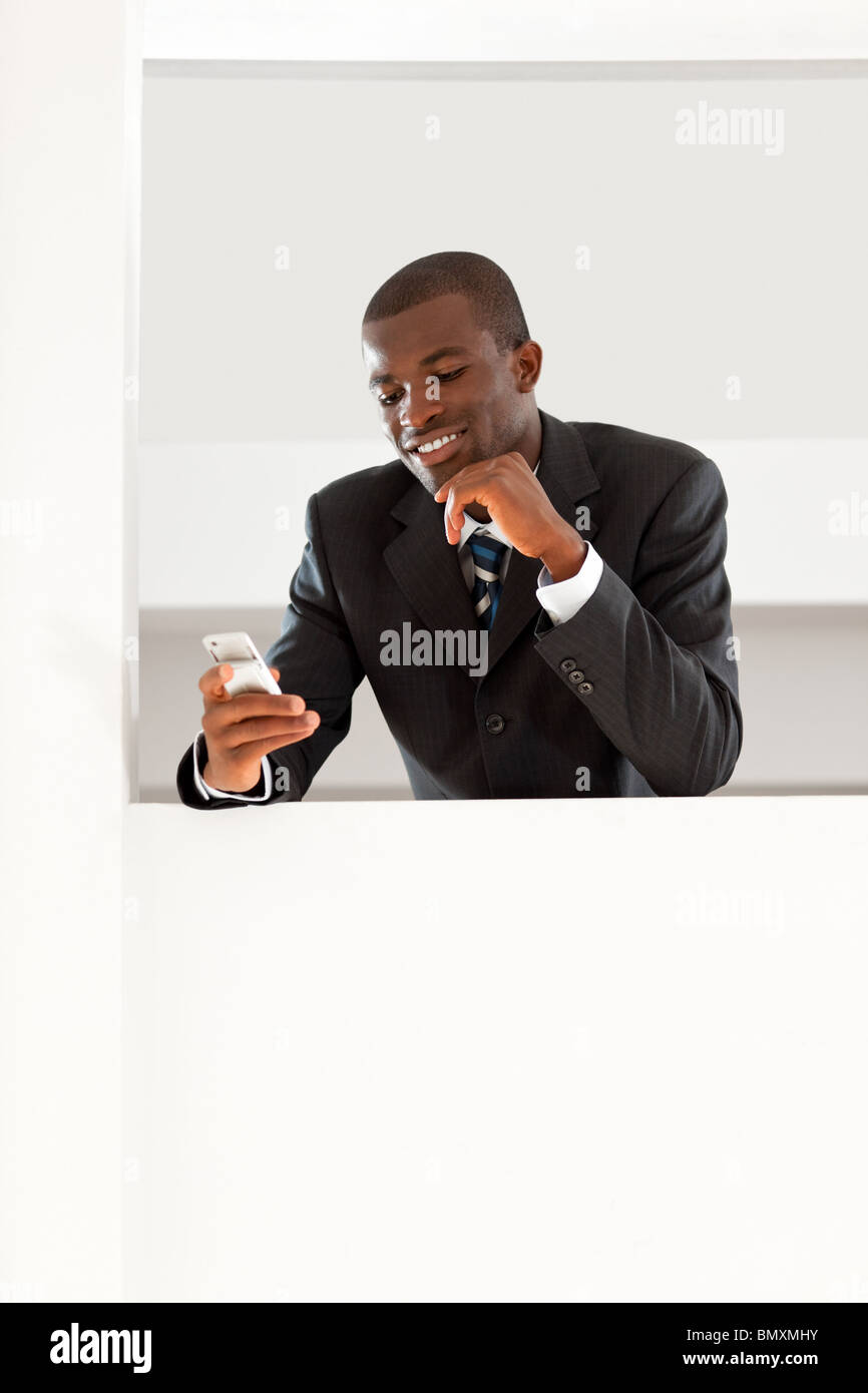 young adult afro-american businessman reading emails on his smartphone indoors. Copy space - Stock Image