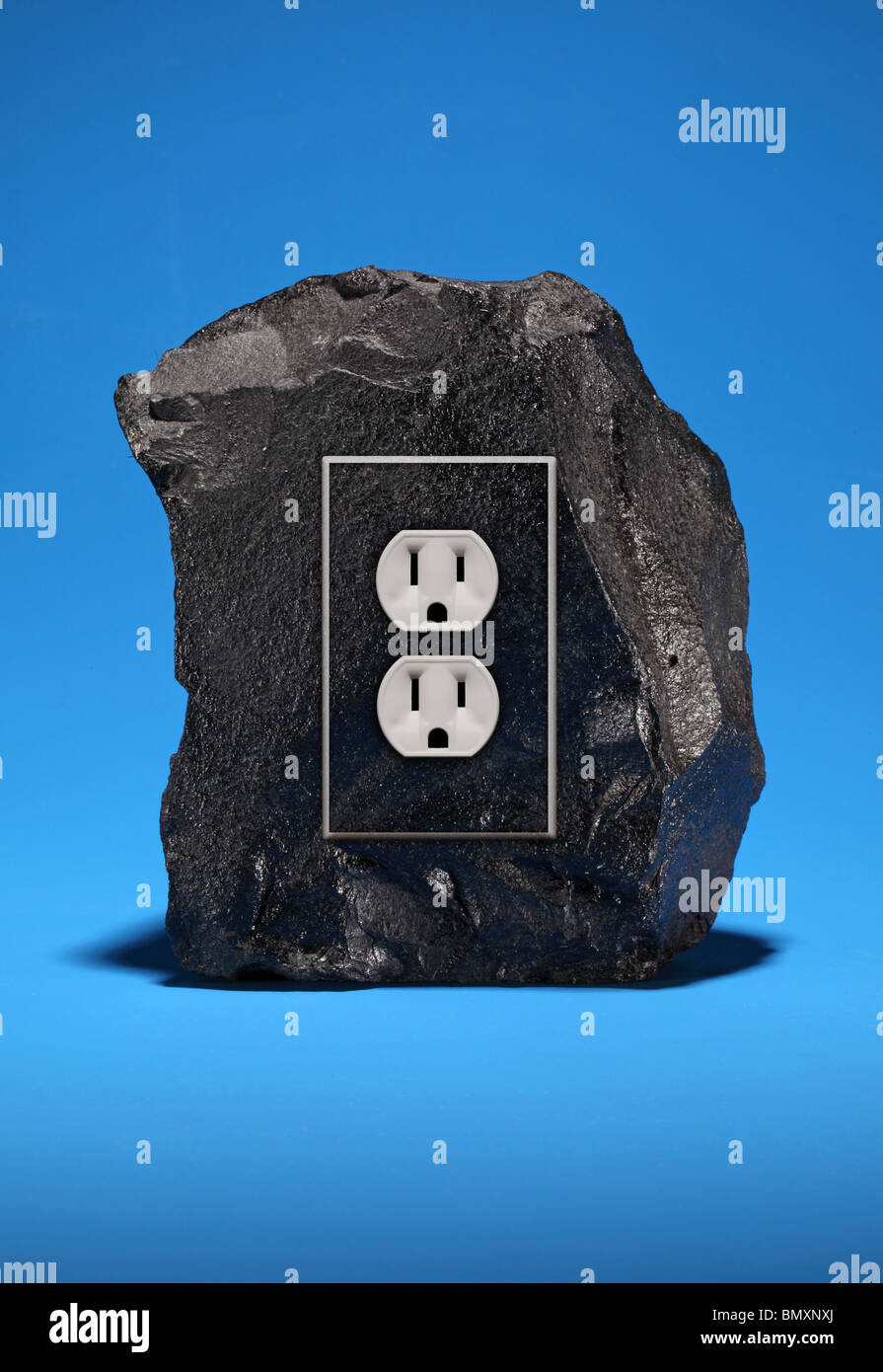 A large black chunk of coal with an electrical power outlet fixture ...
