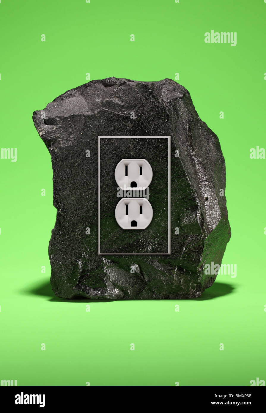A large black chunk of coal with an electrical power outlet fixture on a bright green background. - Stock Image