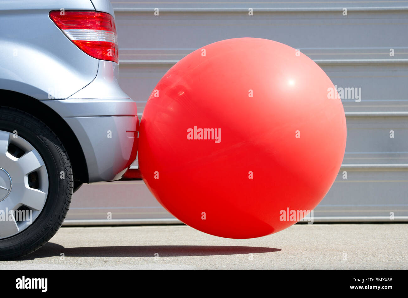 Rear of a car with a baloon on the exhaust pipe - Stock Image