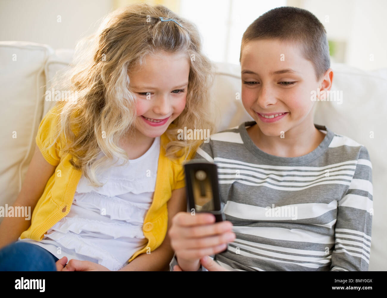 Siblings looking at cellular phone - Stock Image