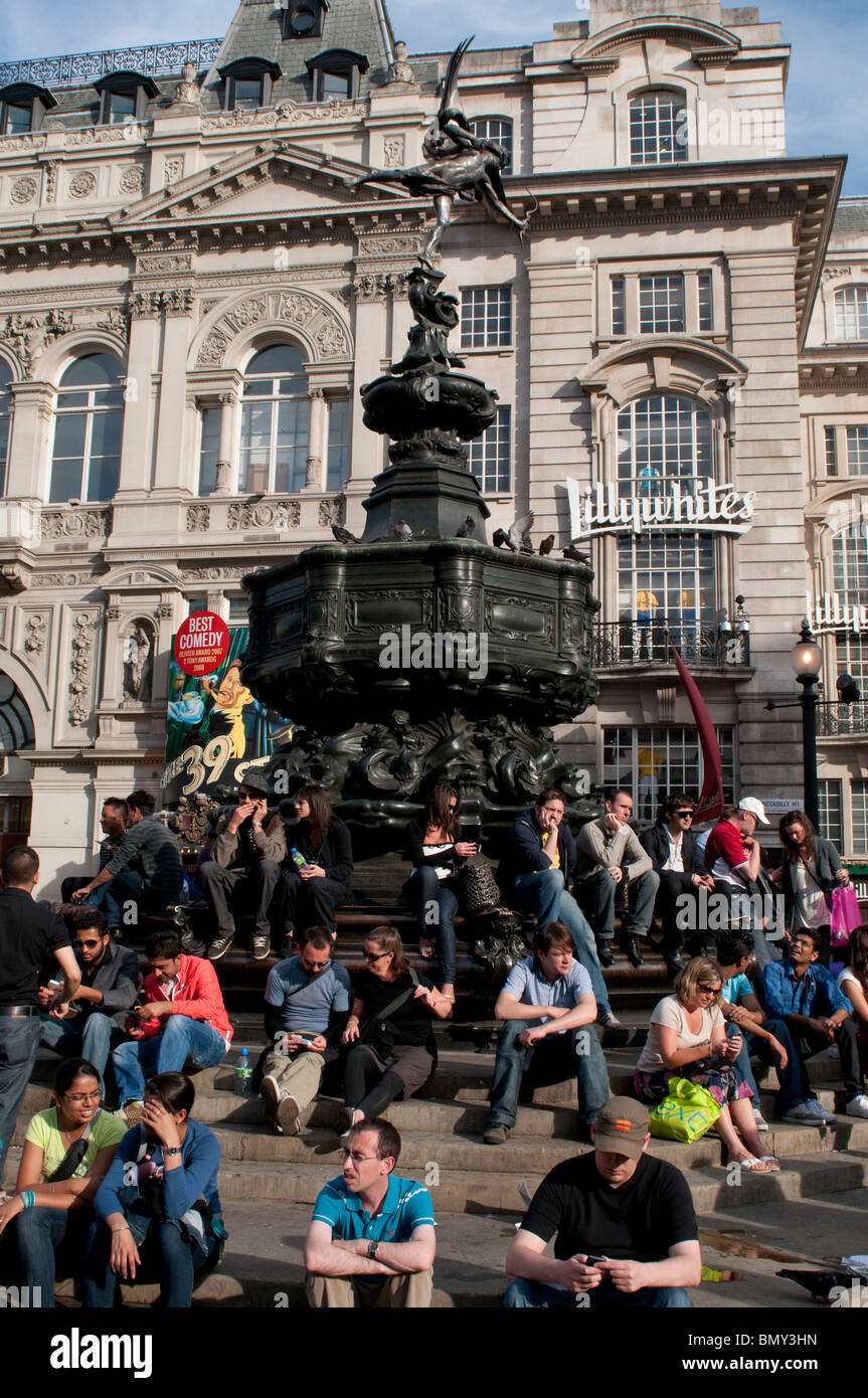 People sitting around Eros statue at Piccadilly Circus, London W1, UK - Stock Image