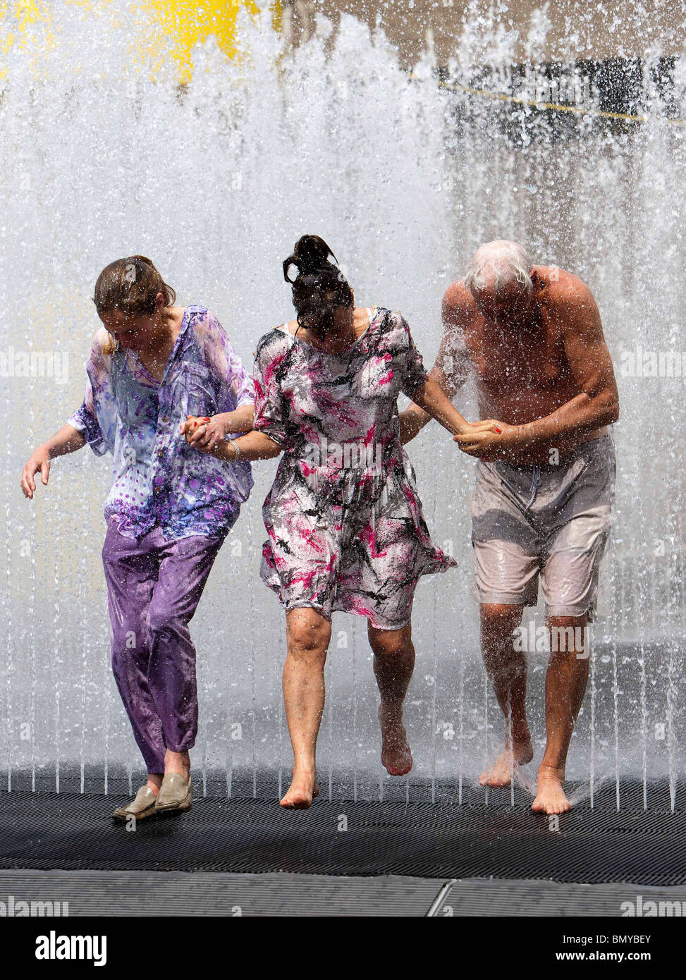 People cooling off in a fountain outside the Royal Festival Hall during hot weather in London - Stock Image