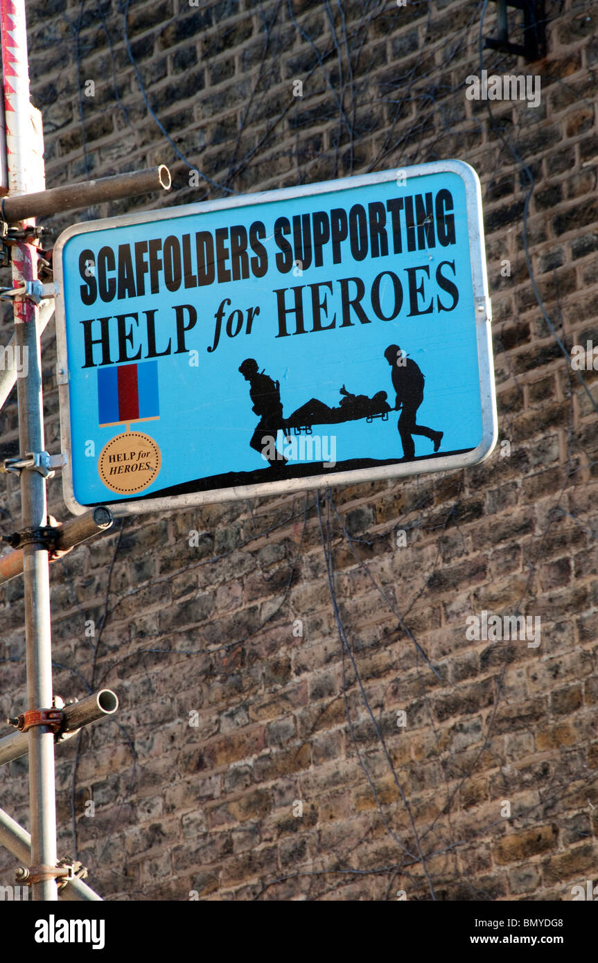 Scaffolders Supporting Help for Heroes sign on a building site in South London - Stock Image