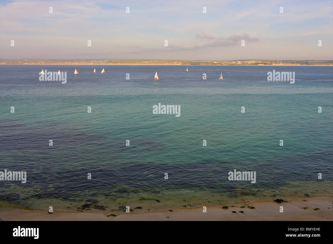 Sailing boats sail across St.Ives bay during a gorgeous summers evening - Stock Image