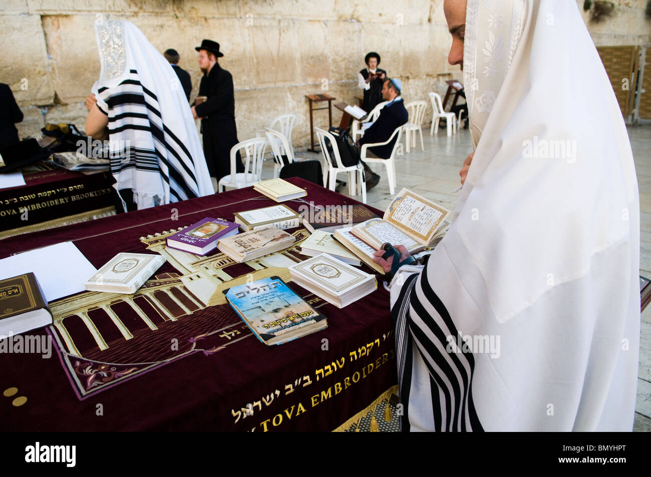A Jewish man praying at the wailing wall in the old city of Jerusalem. he is wearing a Talit and he has Tfilin on - Stock Image