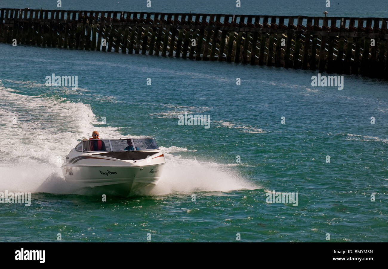 A powerboat speeding into Littlehampton Harbour in West Sussex. - Stock Image
