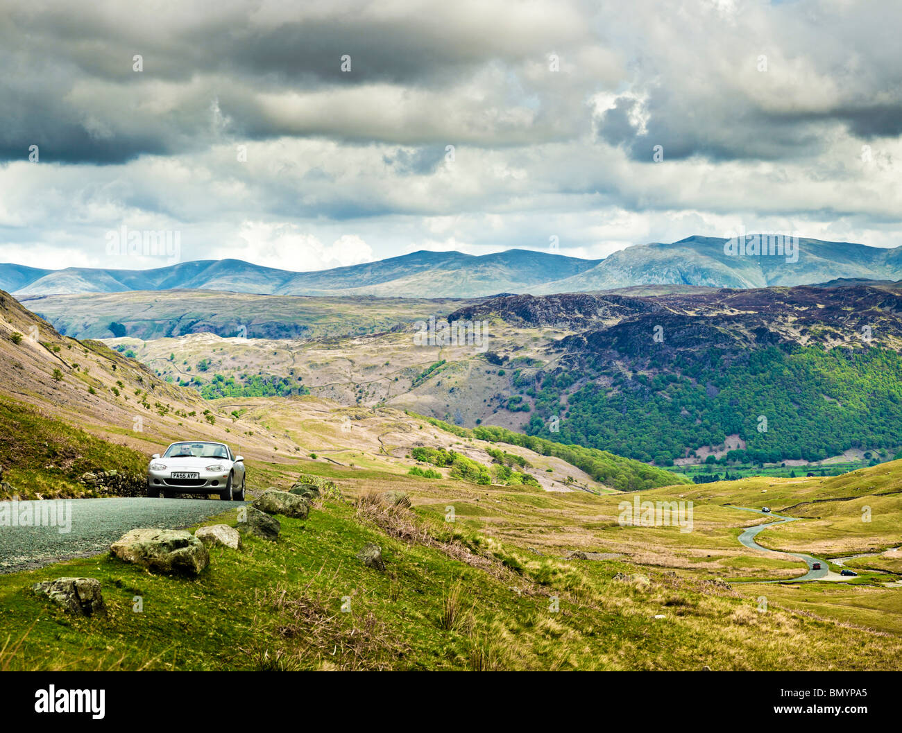 Sports car driving on Honister Pass in the English Lake District National Park, Cumbria, England, UK - Stock Image