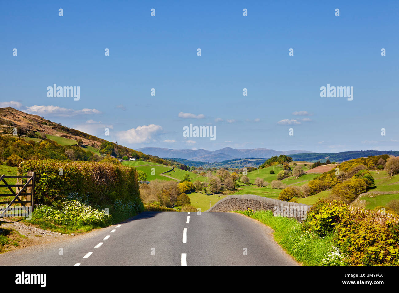 Country road, through English countryside towards the Lake District mountains on a road trip in Cumbria, England, - Stock Image