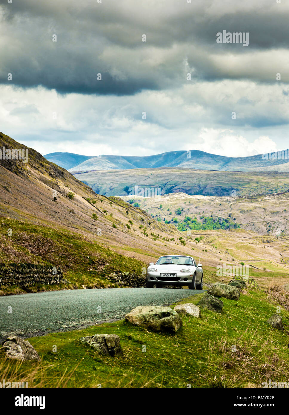 Driving, UK, Sports car driving on a mountain road in The Lake District, on a road trip in Cumbria, England, UK - Stock Image