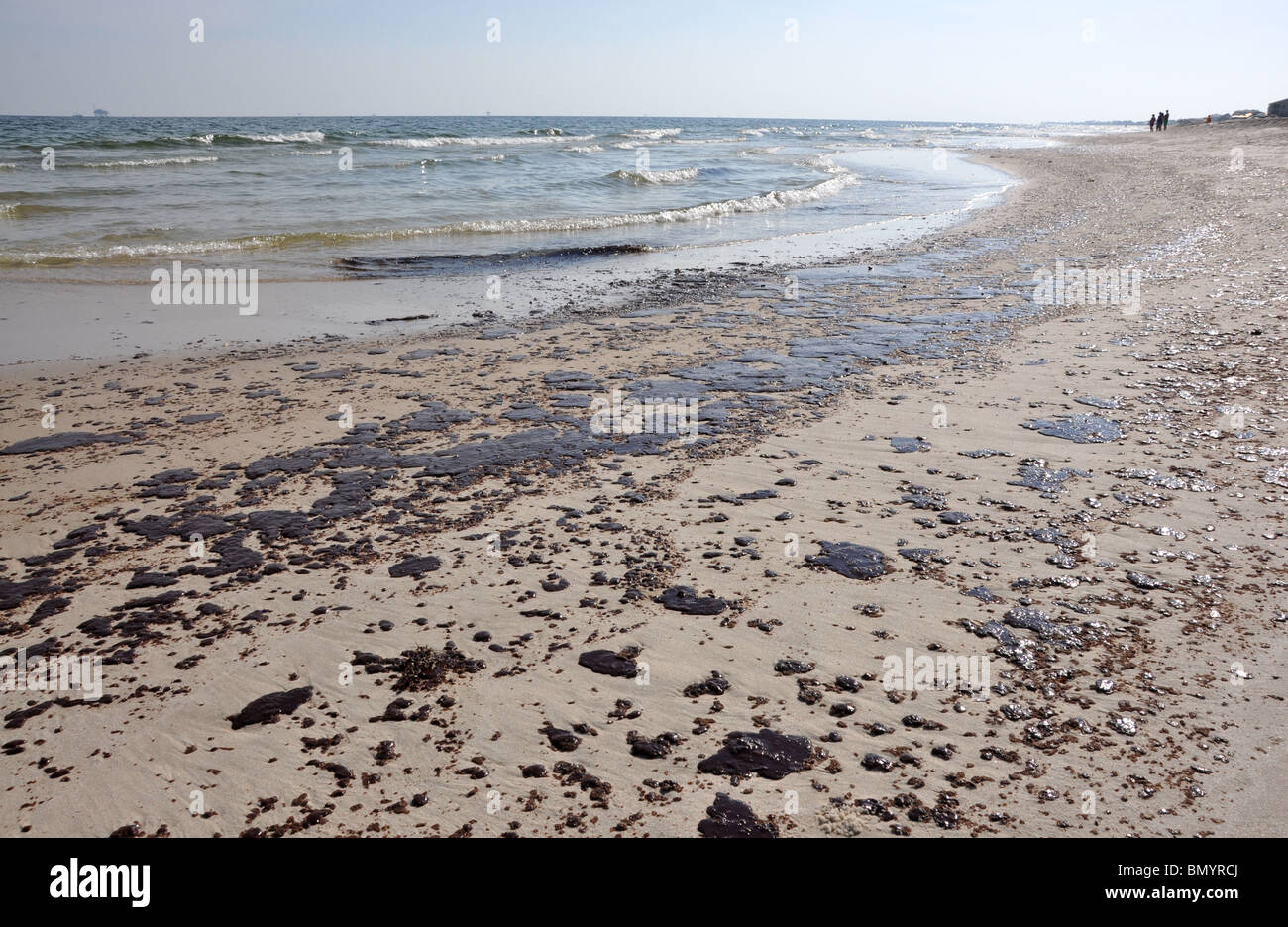 Oil spill on beach with off shore oil rig in background. - Stock Image