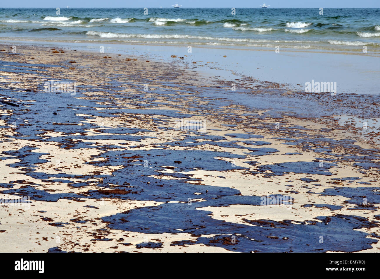 Oil spill on beach with oil skimmers in background. - Stock Image