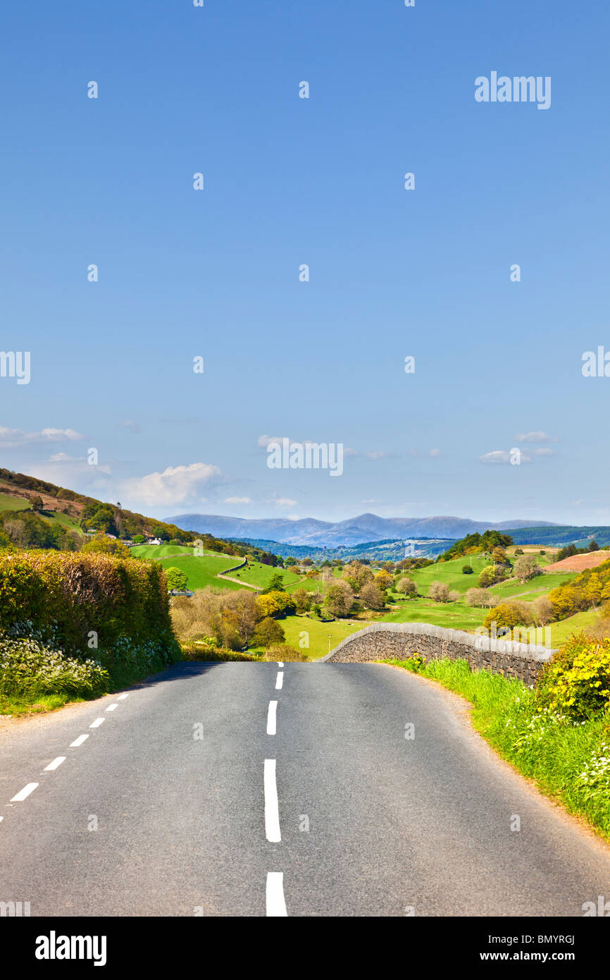 Open scenic road through English countryside towards the Lake District mountains on a road trip in Cumbria England - Stock Image