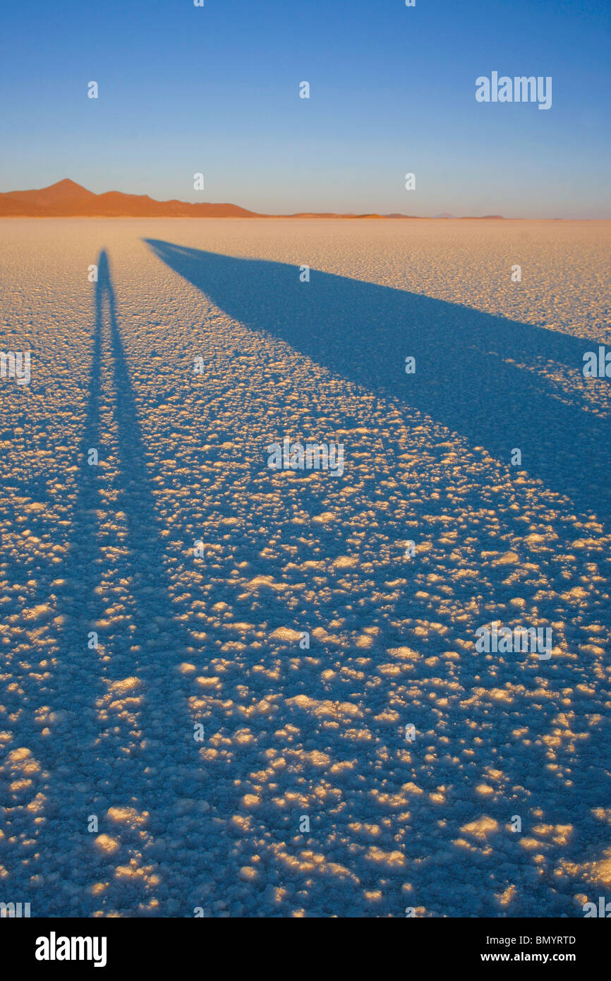 Shadow of the photographer and vehicle at dawn on the Salar de Uyuni in Bolivia Stock Photo