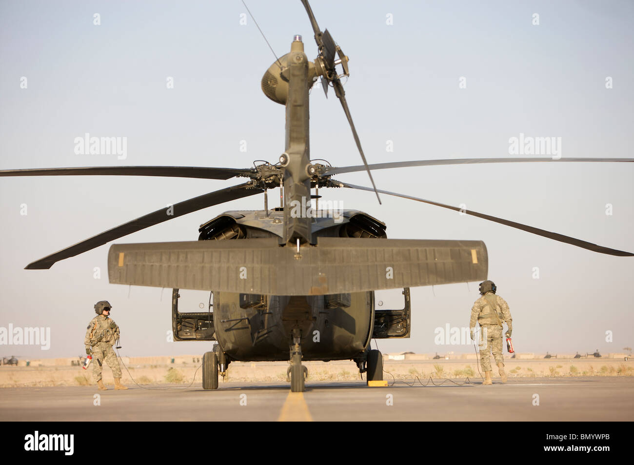 Crew Chiefs stand beside their UH-60L Black Hawk helicopter. - Stock Image