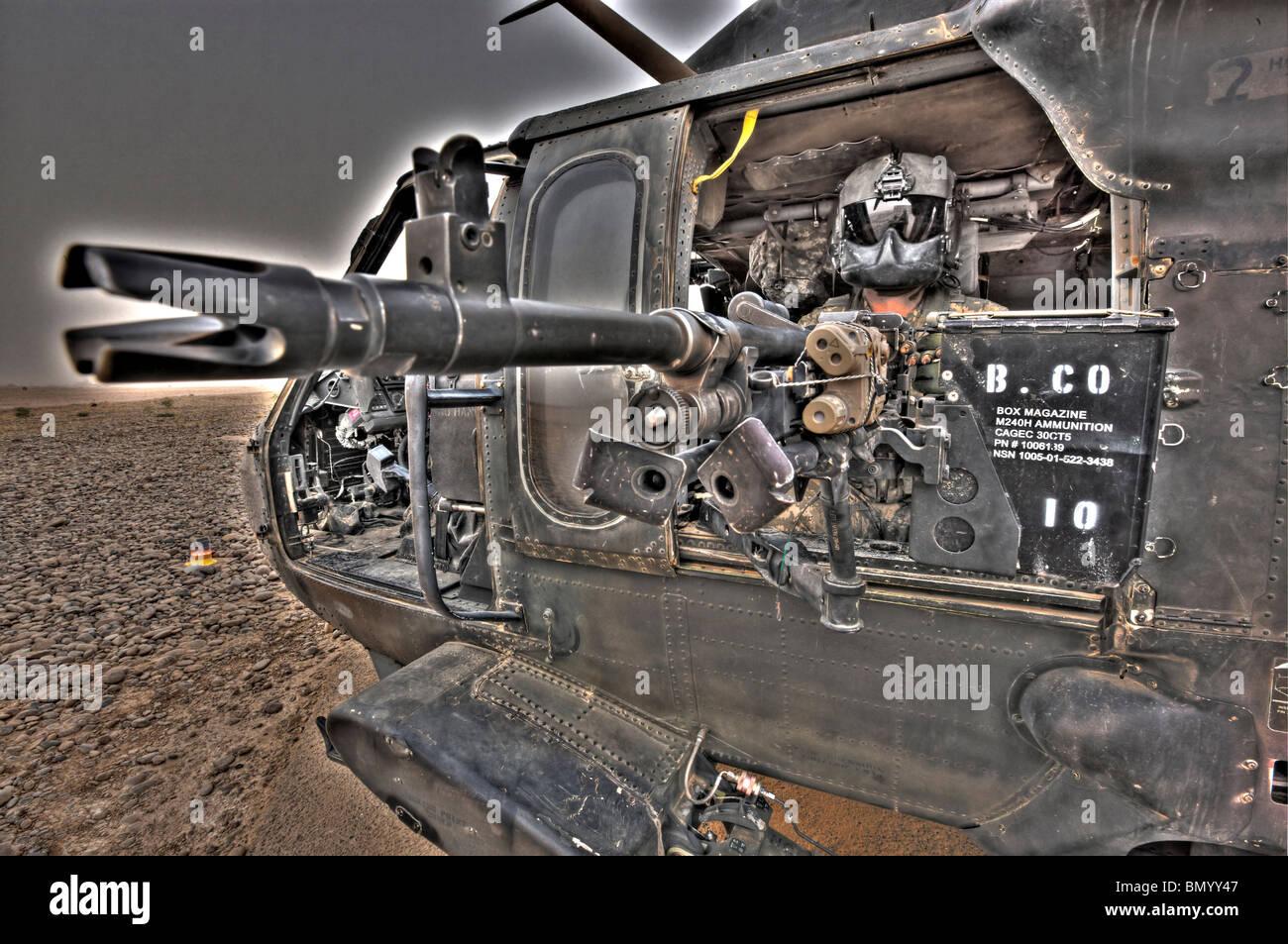 A high dynamic range image of a UH-60 Black Hawk door gunner manning a M240G medium machine gun. - Stock Image