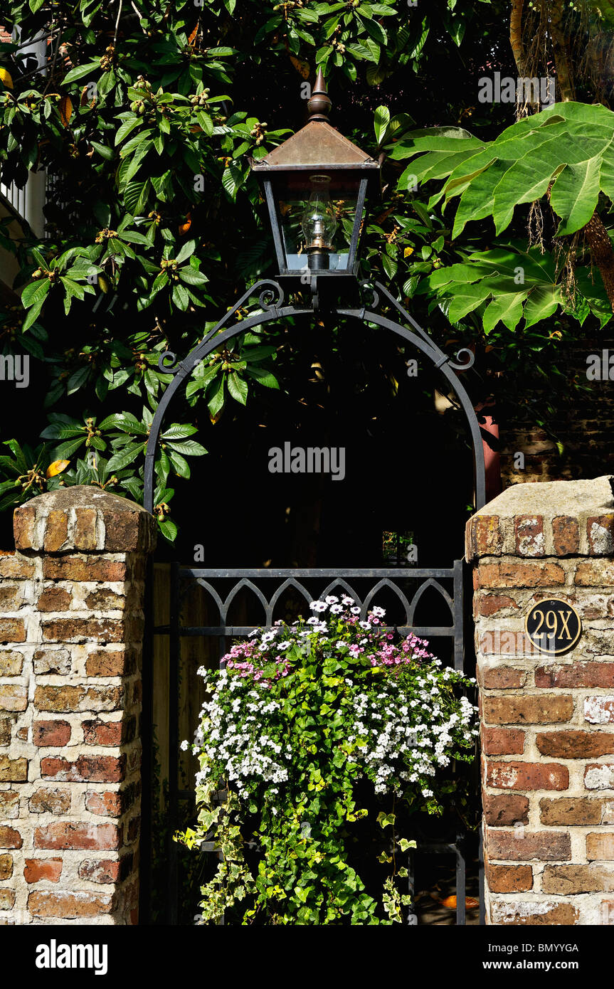 Wrought Iron Garden Gate, Gas Lamp and Flowers in the French Quarter of Charleston, South Carolina - Stock Image