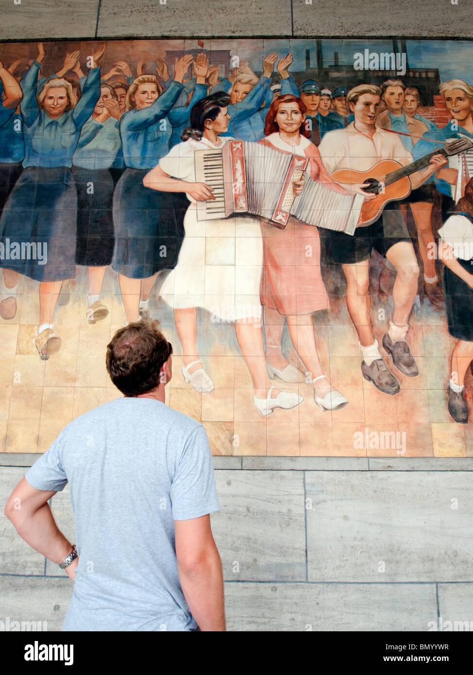 East German era socialist propaganda murals of happy workers on wall of German Finance Ministry building in Berlin - Stock Image
