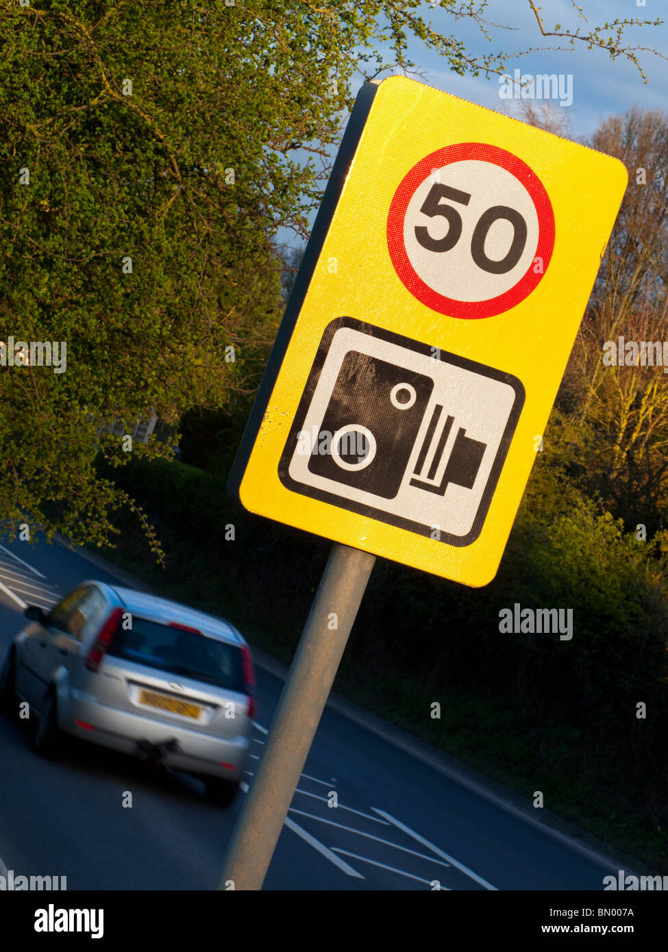 Speed camera warning sign and 50mph speed limit notice on a British road Stock Photo