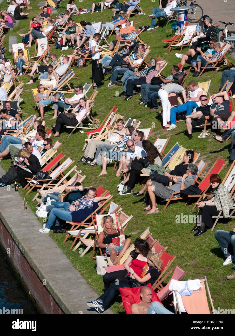 Busy waterside café in summer beside Spree River in central Mitte Berlin Germany - Stock Image