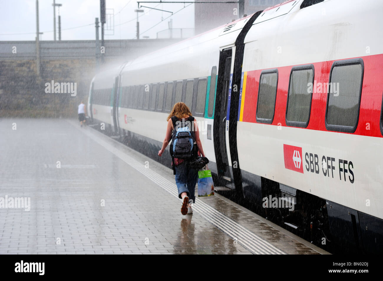 A passenger running through a torrential downpour at Basel railway station. - Stock Image