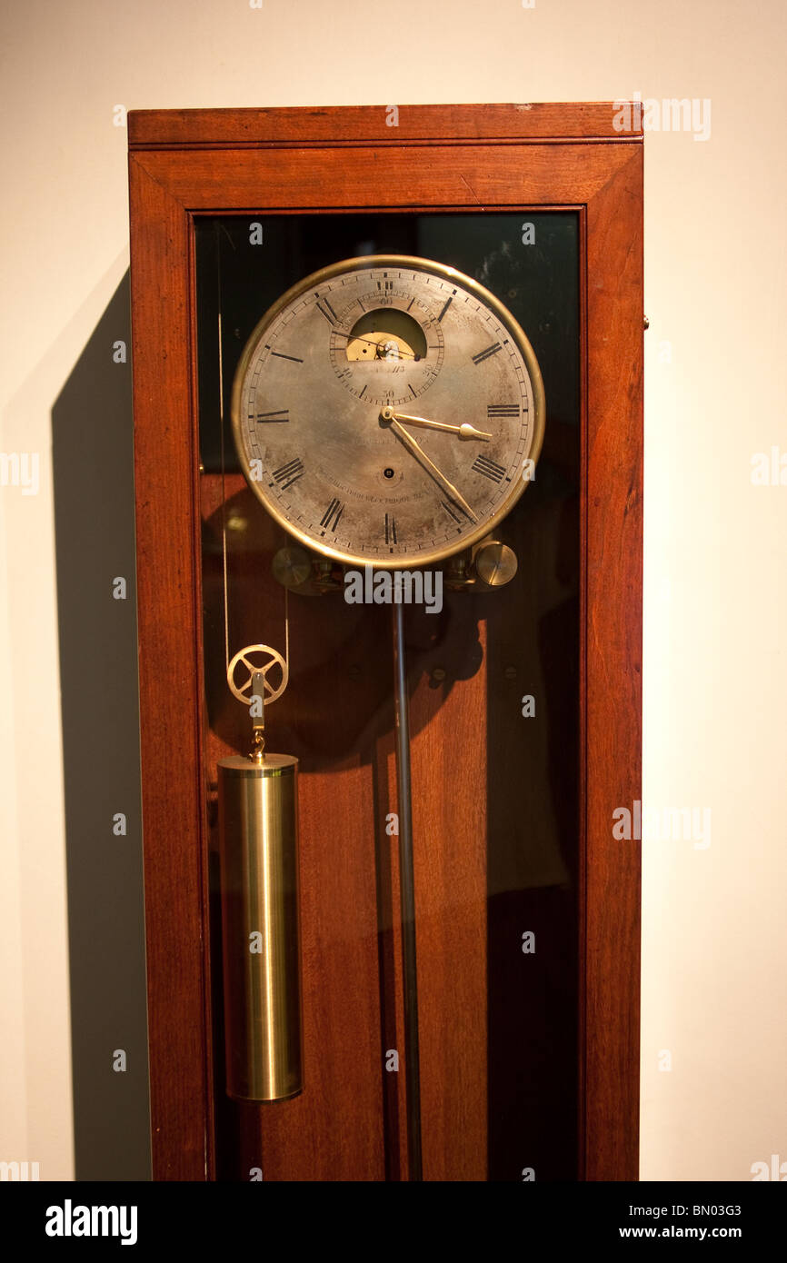 antique old roman numeral mechanical wall clock - Stock Image