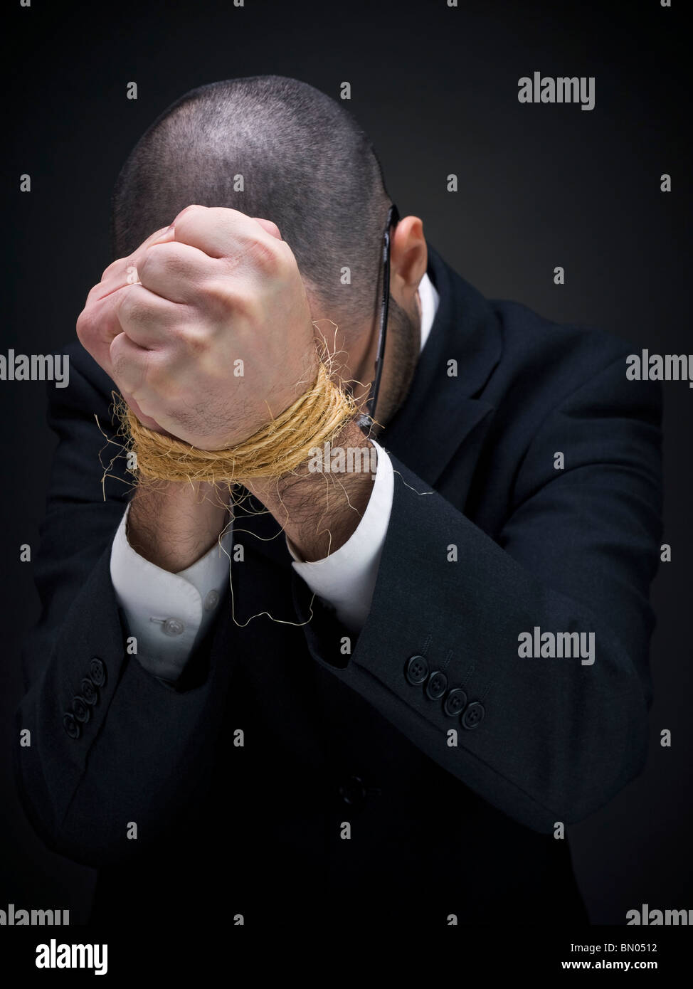A man on a suit is raising his tied hands. - Stock Image