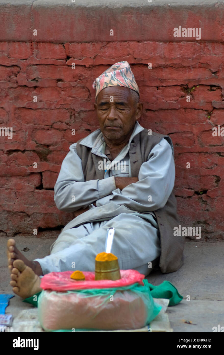 An old man dozes while waiting for people to buy his tumeric powder in Durbar Square, Kathmandu, Nepal. - Stock Image