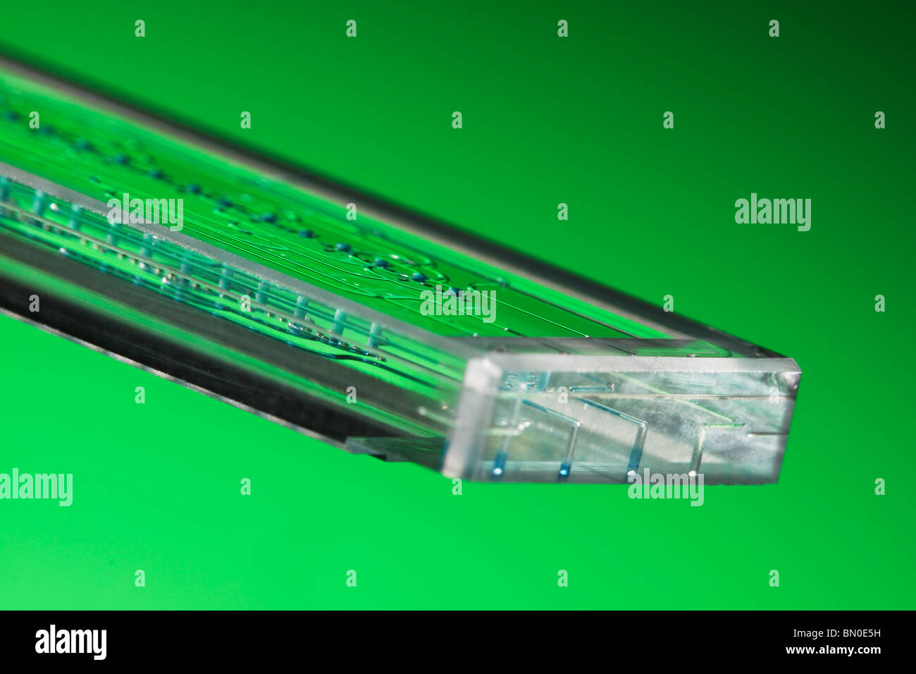 Microfluidic etched glass microreactor chip mixing mutiple fluid streams of liquids in micro & nano technology - Stock Image