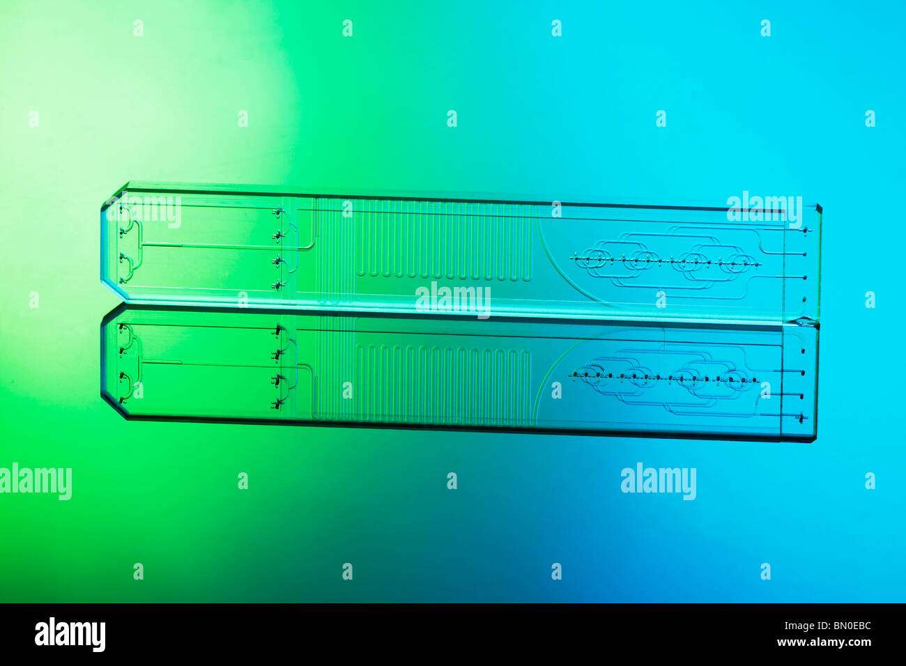 Microfluidic etched glass microreactor chip mixing mutiple fluid streams of liquids in micro and nano technology - Stock Image