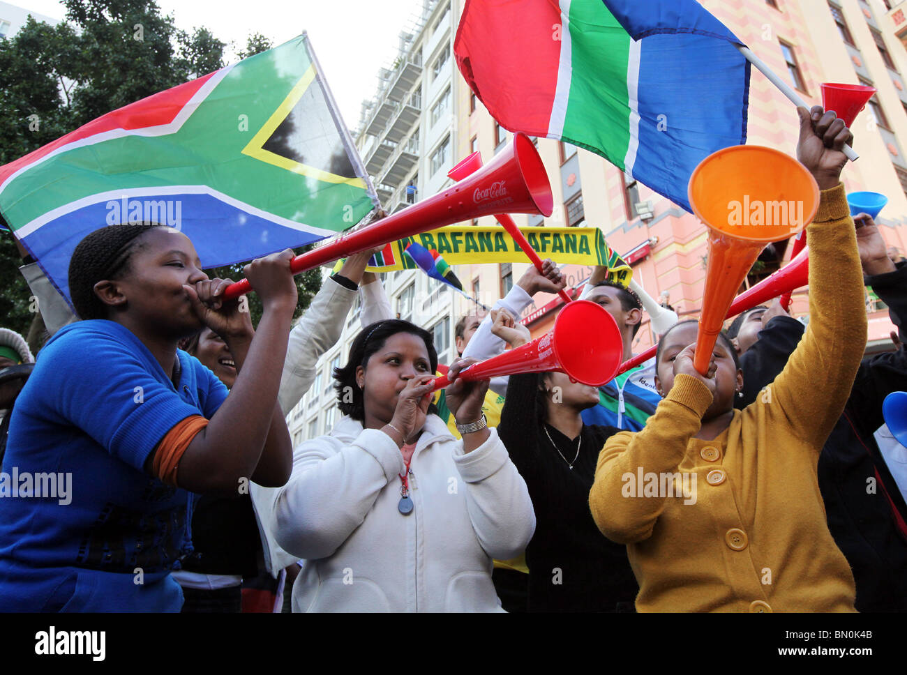 South African soccer fans blow their Vuvuzelas at the Green Market Square in Cape Town - Stock Image