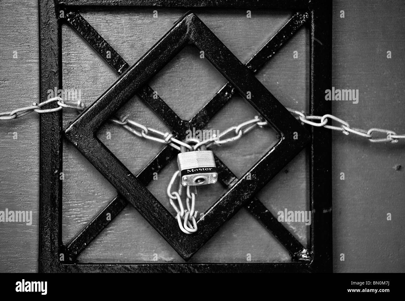 Ybor City, Tampa, FL - July 2009 - Padlocked chain woven through wrought iron gate in Ybor City area of Tampa, Florida - Stock Image