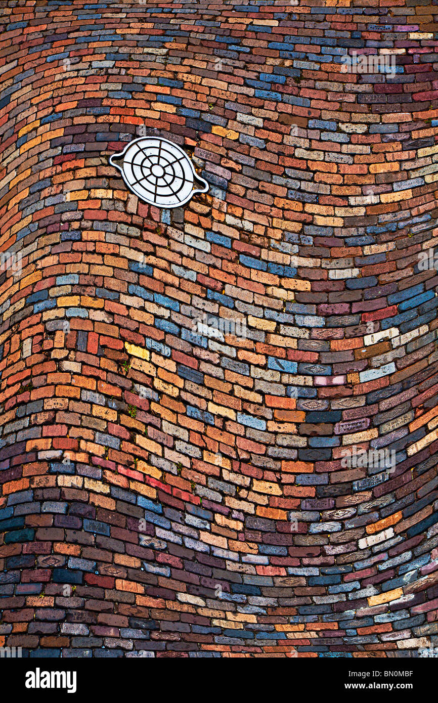 Warped image of cast iron utility handhole in colorful brick paved street at Ybor City area of Tampa, Florida - Stock Image
